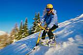Woman snowbiking downhill, Serfaus, Tyrol, Austria