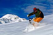 Young man snowscooting downhill, Serfaus, Tyrol, Austria