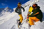 Two young people talking, snakeboarding in snow, Serfaus, Tyrol, Austria