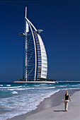 Woman walking along the beach near Hotel Burj-al-Arab, Dubai, United Arab Emirates