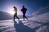 A couple jogging on a snow covered track, Austria