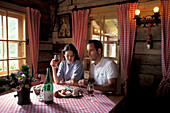 Couple having a meal in an alpine hut, South Tyrol, Italy, Europe