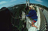 Woman bungee jumping from a bridge, France
