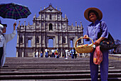 Vendor in front of Sao Paulo cathedral under blue sky, Macao, China, Asia