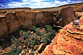 A man sitting at the edge of Kings Canyon, Kings Canyon National Park, Northern Territory, Australia