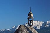 Chapel's tower and bell in front of mountains, Winkelmoosalp, Bavaria, Germany