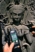 A man measuring the temperature of a relief, Angkor Wat, Siem Raep, Cambodia, Asia