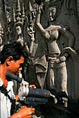 A man reparing a relief, Angkor Wat, Siem Raep, Cambodia, Asia