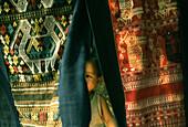 Child hiding behind Lao textiles, Luang Prabang, Laos, Indochina, Asia