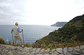 A woman enjoying the views while hiking, Cinque Terre, Italy
