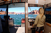 Eine Frau fährt ein Boot, Lake Powell, Arizona, Utah, USA