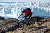 Ein Mann beim Mountainbiken über Felsen, Jakobshavn, Ilulissat, Grönland