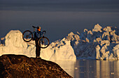 A Mountainbiker carrying her bike over rocks in the midnight sun, Jakobshavn, Ilulissat, Greenland