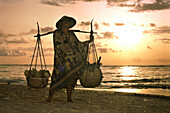 Fruit vendor on the beach at sunset, Lombok, Bali, Indonesia, Asia