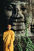 Monk in front of a figure of the Bayon temple, Angkor, Siem Raep, Cambodia, Asia