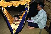Man singing a child to sleep, Penang, Malaysia, Asia