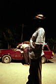 Two jamaican men standing in front of a red car at night, Jamaica, Carribean
