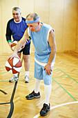 Mature men playing basketball