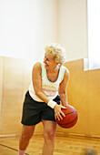 Mature woman playing basketball