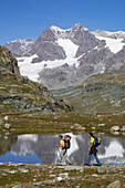 Two young women hiking in the mountains in front of a lake, Veltlin, Italy