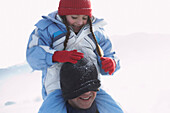Father carring his daughter on shoulders, pulling knit hat over man´s face
