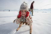 Man pulling daughter in toboggan on snow