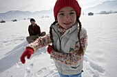 Daughter pulling her father in toboggan on snow