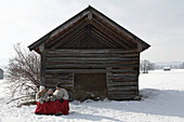Parents and son sitting near wooden hut, warming with red blanket