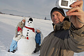 Familiy and snowman, father photograhing