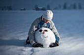 Boy hugging head of snowman, kneeing