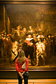 Visitor looking at painting The Night Watch by Rembrandt, Rijksmuseum, Amsterdam, The Netherlands