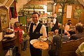 Waiter serving giant Viennese Schnitzel at Restaurant Figlmueller, Vienna, Austria