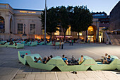 People sitting in a bar in front of Kunsthalle Wien at MuseumsQuartier in the evening, Vienna, Austria