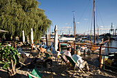 People sitting in deck chairs at harbour, People sitting in deck chairs at sandy open-air area of restaurant at Oevelgoenne, Hamburg, Germany