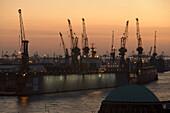 Dockyard with cranes in the dusk, Landungsbruecken, St. Pauli, Hamburg, Germany