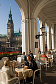 People at Alsterarkaden and view to the guildhall, People sitting in an open-air cafe at Alsterarkaden with view to the guildhall, Hamburg, Germany