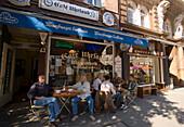 People sitting outside of Cafe Uhrlaub at St. Georg street, Hamburg, Germany