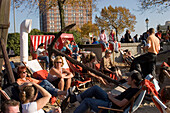 People sitting in deck chairs at Museumshafen, People sitting in deck chairs of an open-air cafe at sandy beach of Museumshafen oevelgoenne, Hamburg, Germany
