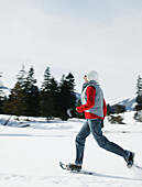 Young woman running with snowshoes in winter landscape