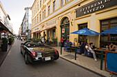 Ragtop passing a open-air restaurant , A black ragtop passing a open-air restaurant at Raday Street, Pest, Budapest, Hungary