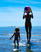 Mother and daughter playing with beach ball