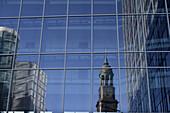 Bell tower of Michel, St. Michaelis Church in window reflection, Hamburg, Germany