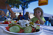 People eating greek salad in restaurant, Karpathos, Dodecanese Islands, Greece