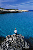 Boy standing on rock, coast near Fontana Amorosa, Akamas peninsula, Cyprus