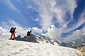 Frau und Mann wandern auf Schneefeld vor Bergkulisse. Pass da Casnil, Bregaglia, Bergell, Graubünden, Graubuenden, Schweiz, Alpen.