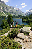 Two hiking women taking a rest in front of a mountain lake Laegh Cavloc, Cavloc Lake, Forno, Bergell, Graubuenden, Grisons, Switzerland
