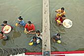 Women vendors standing waist-high in river, carrying fruit, Myanmar