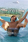 Young man having fun in water slide