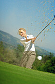 Young woman with blond hair hitting golf ball on the golf course