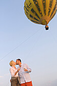 Couple kissing in front of hot air balloon